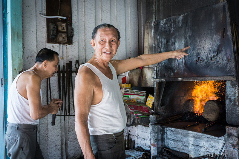 Blacksmith Sri Gading - Mr Lai pointing at the fire in forge