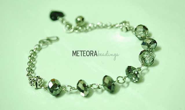 Bracelet - grey beads, with silver chain, bell, flower connector and love charm