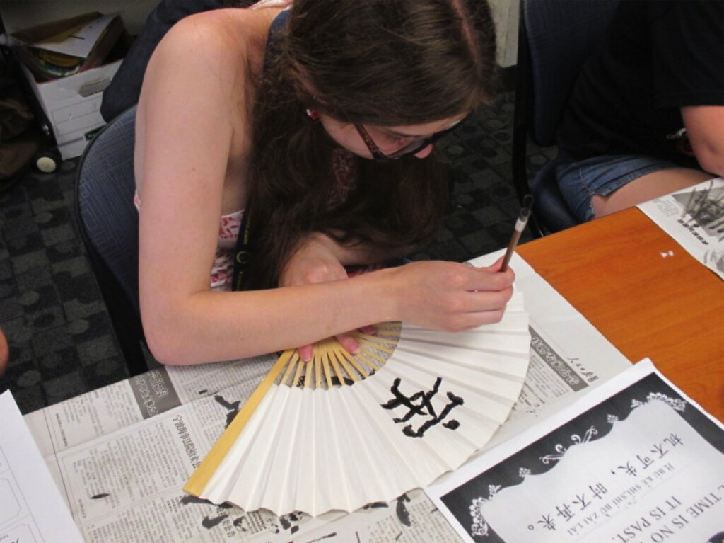 Student of the Chinese foreign language academy decorating a paper fan with calligraphy.