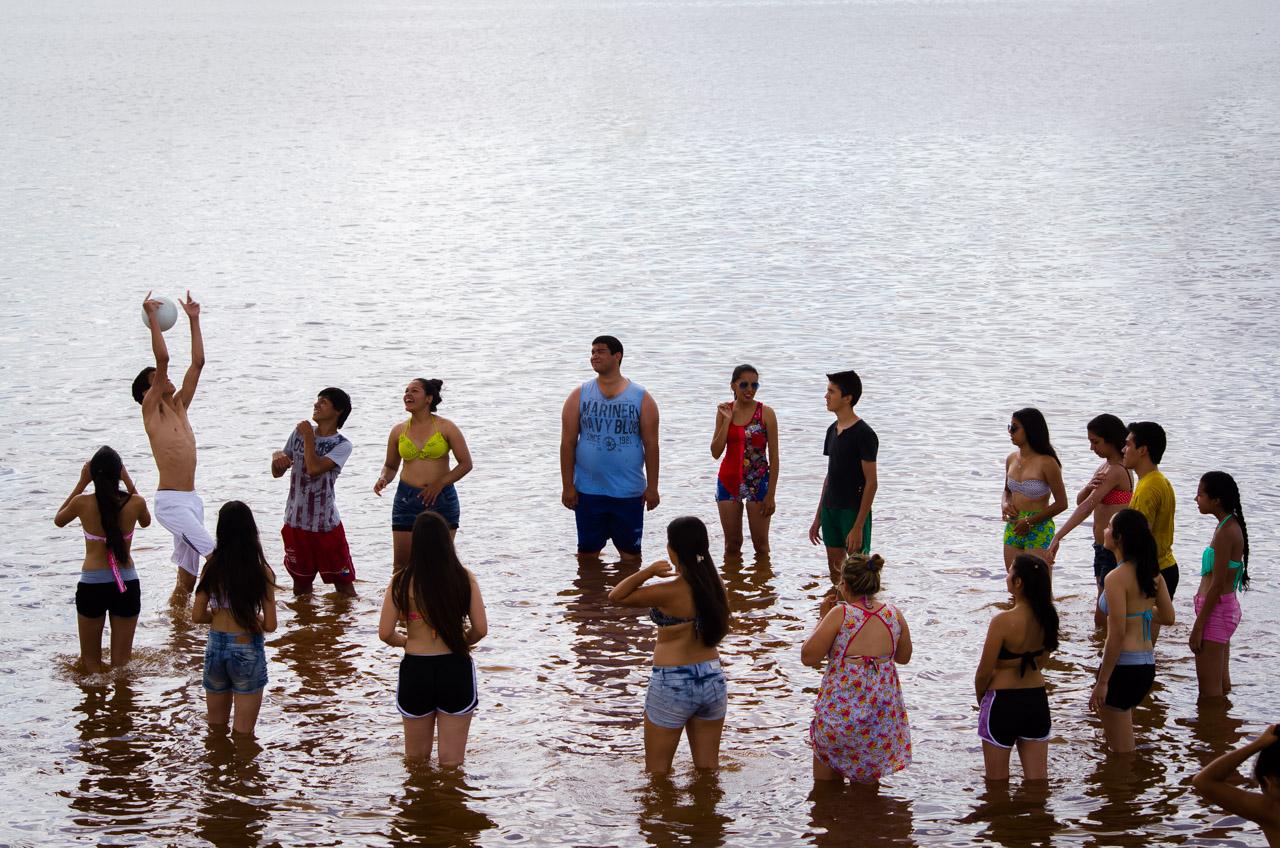 Un grupo de jóvenes se divierten con el juego de no dejar caer la pelota, en las aguas de la playa San José de Encarnación. (Elton Núñez)