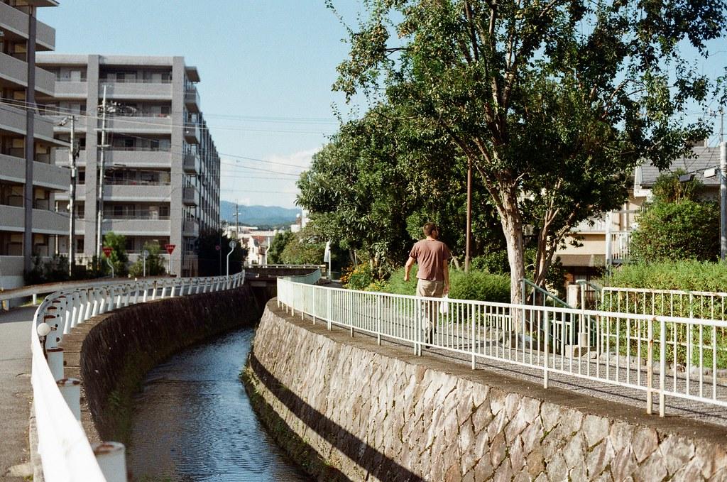白川通 Kyoto / Kodak ColorPlus / Nikon FM2 2015/09/27 在白川通停留很久,我記得那時候坐在路邊換底片,但是周圍的安靜讓我繼續坐著休息,沒有急著離開。  沿著河堤走,因為高度的關係,可以用一種凌空的角度偷偷觀察這個時段人們的生活。  老實說,京都真的是一個可以待很久的地方,即使現在回憶起來,還可以感受到當時的安靜與溫暖的陽光。  雖然在河堤上走著走著會有一點點小孤單。  Nikon FM2 Nikon AI Nikkor 50mm f/1.4S Kodak ColorPlus ISO200 0987-0004 Photo by Toomore