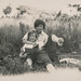Small photo of Two affectionate women reading in a field