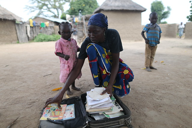 "Rifkatu Sanda, mother of Lugwa Sanda, displays Lugwa's school books in front of her home in the village of Kuburmbula<br /> <br /> ""No one wants to sleep in her room.""<br /> <br /> Two weeks after Rifkatu gave birth to her 10th child, her daughter, Lugwa, was kidnapped. ""When I heard, I lost myself completely,&quot; Rifkatu said. <br /> <br /> Lugwa, who had just turned 17 at the time, liked to play with the baby in the room she shared with her sister.<br /> <br /> ""We had all heard of Boko Haram, but we just didn't think they would get to us, so we were not afraid of Boko Haram,"" her mother said.<br /> <br /> But Boko Haram did get to them in the most brutal, most horrific manner. After the abduction, not even Lugwa's sister wanted to sleep in the room the two girls once shared."