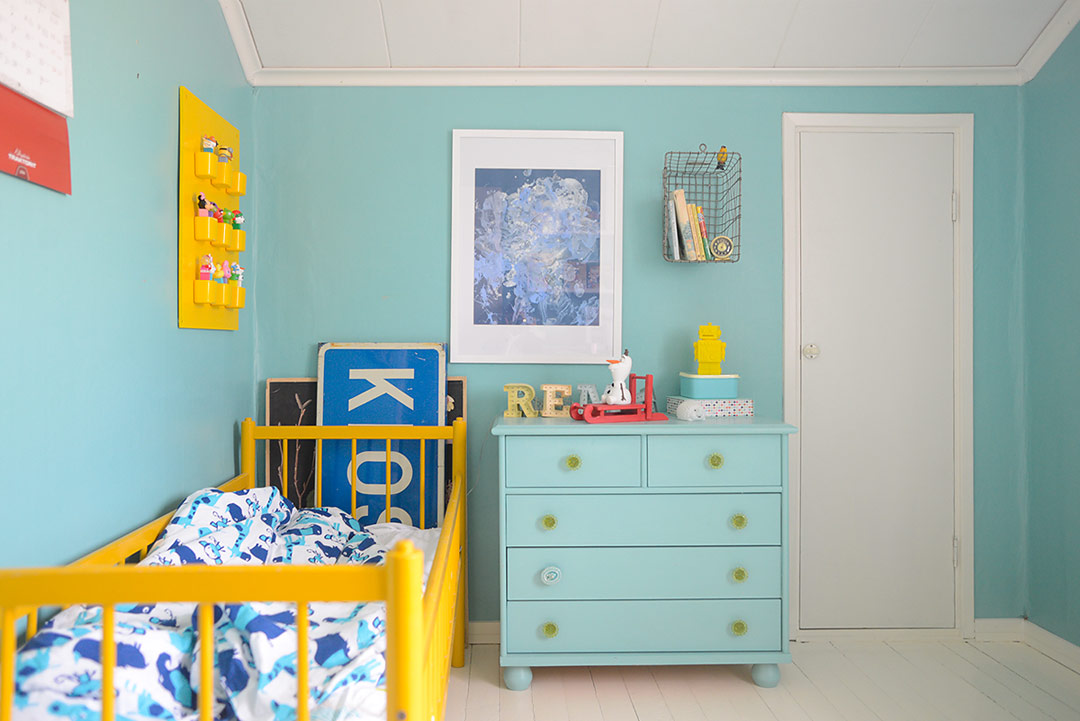 Yellow vintage kids' bed in a turquoise room
