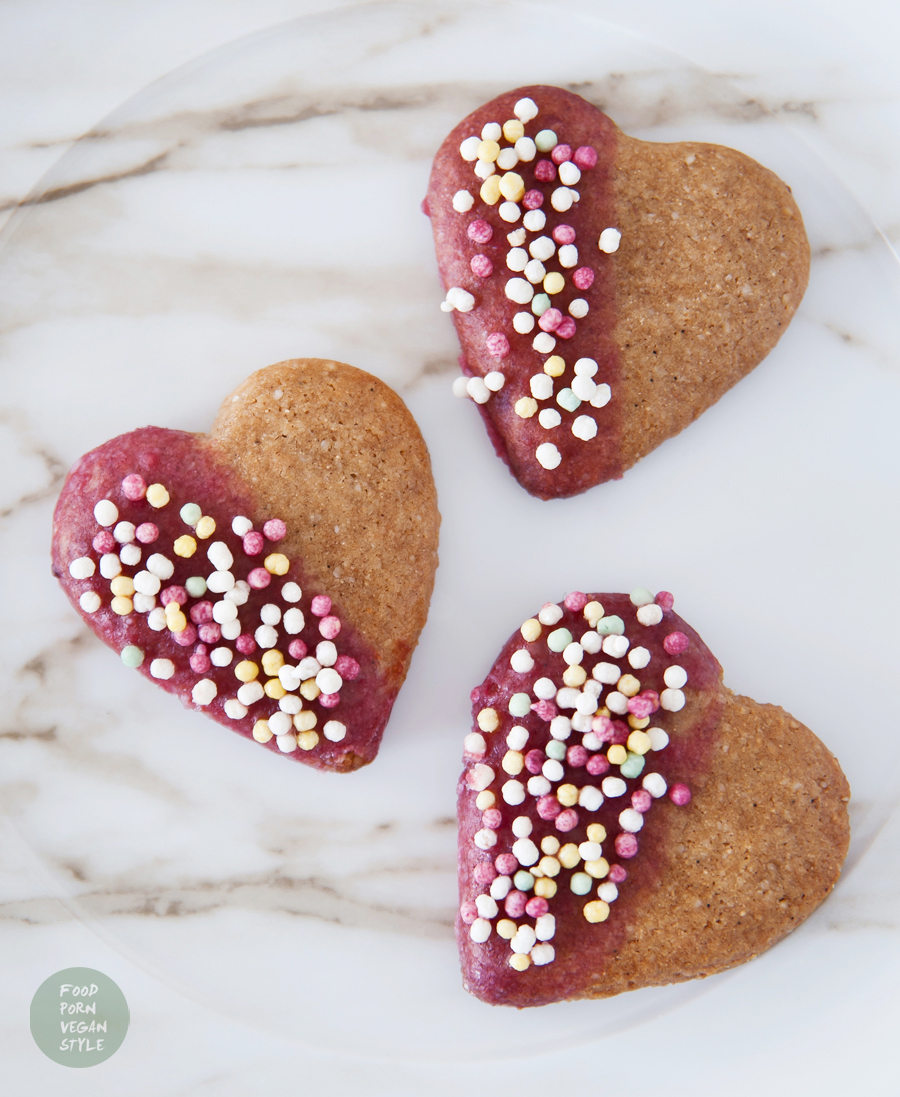 Vegan almond-chestnut cookies 'hearts' with pink icing and colorful sprinkles