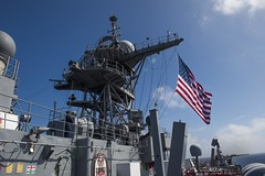 Sailors aboard amphibious dock landing ship USS Ashland (LSD 48) raise the ensign while navigating the waters of the South China Sea. (U.S. Navy/MCSN Kelsey L. Adams)