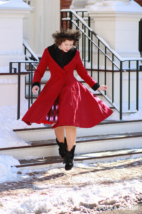 Twirling to show off the full skirt of the Hell Bunny Vivien coat.  Styled with a black feathered hat and Royal Vintage Victoria carriage boots