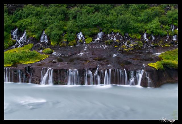 Hilos estrechos y bajos que caen de cascada Hraunfossar