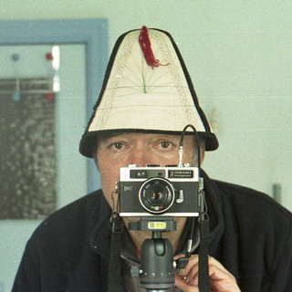 reflected self-portrait with Hanimex Compact R camera and Chinese hat