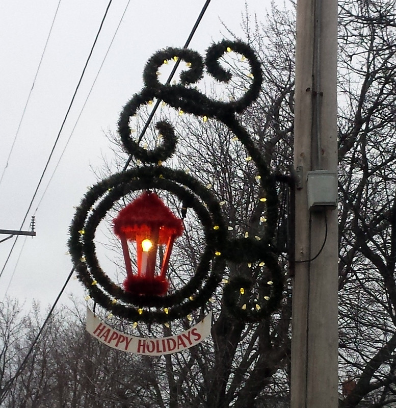red streetlight circled twice by garland, more swirled above, Happy Holidays sign hanging on bottom