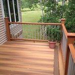 DuraLife Siesta decking in Golden Teak with Railways railing and custom metal balusters