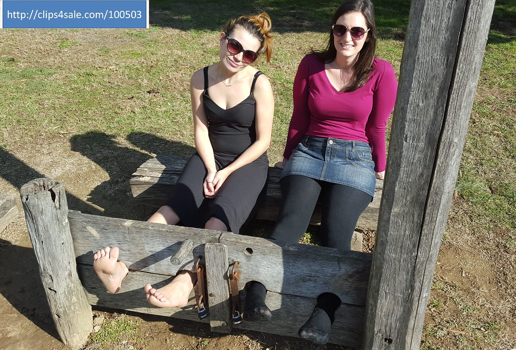 Locked in the stocks pillory in tights and bare feet - a