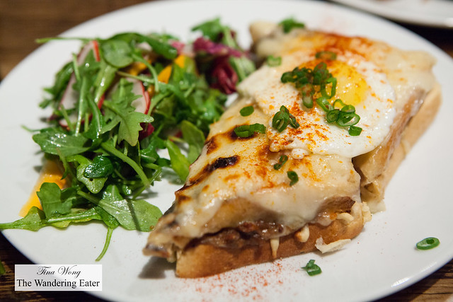 Beef short rib croque madame topped with Emanthal, jalapeño jam, and salad