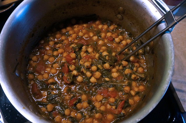 A pot full of chickpeas, spinach, and tomatoes, with a ladle resting in it: if only the internet could transmit smells.
