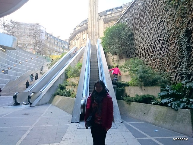 stenoodie standing in front of an outdoor escalator in Paris