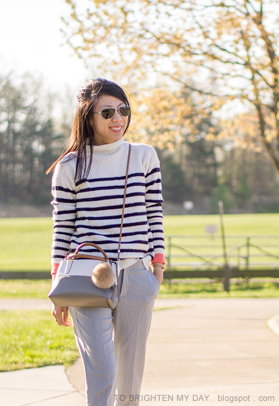 striped sweater, gray pants, colorblocked crossbody bag with fur pom keychain