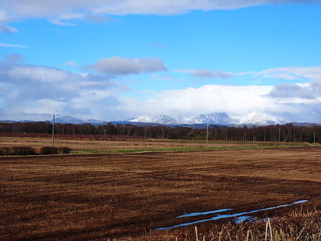 Rural view on sunny day with Coniston snow capped mountains in the distance