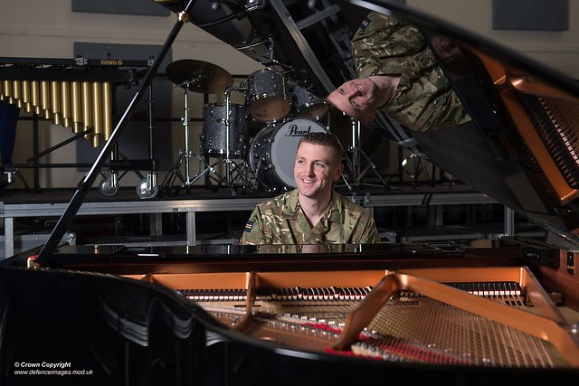 British Army Drum Major seated at a grand piano