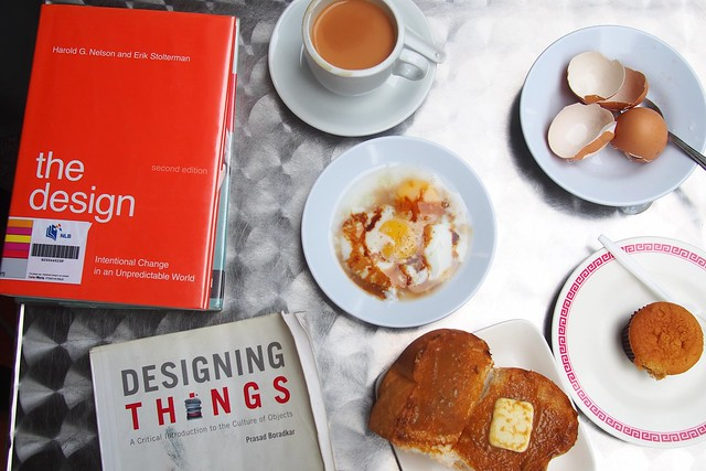 design books and Singaporean Hainanese local breakfast - teh si, kaya toast, soft-boiled eggs, a cupcake