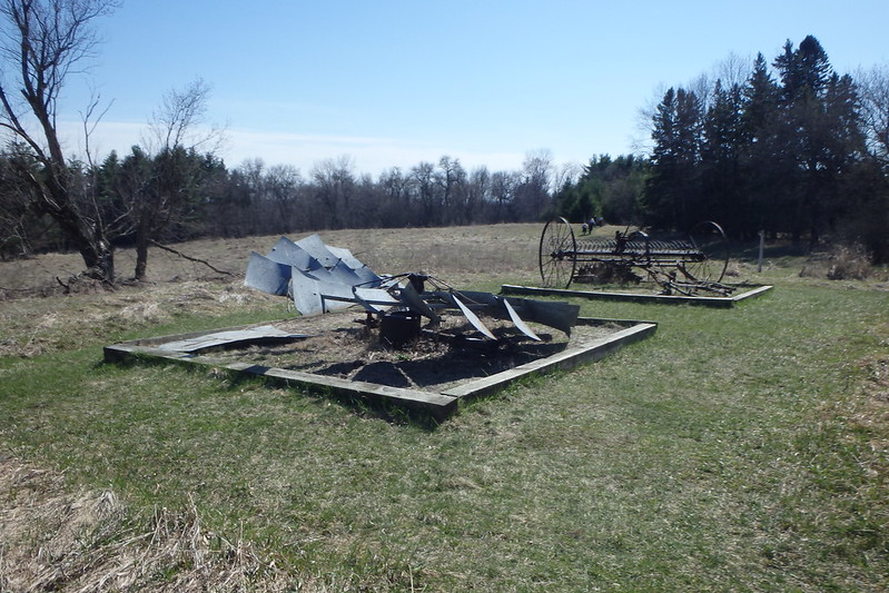 the top of a windmill lying flat on the ground, with a plow in the background, both in a grassy lawn and marked off by boards on the ground