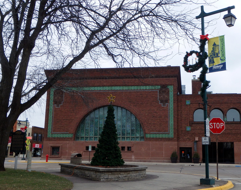 tall tree with a gold tinsel star, in front of the historic bank, and a lightpole with garland and a wreath