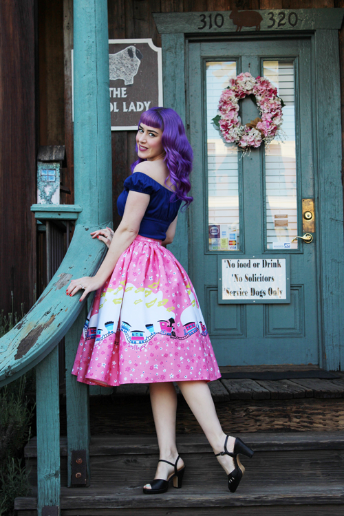 Pinup Girl Clothing Pinup Couture Peasant Top in Dark Royal Blue Jenny Skirt in Mary Blair Pink Train Border Print