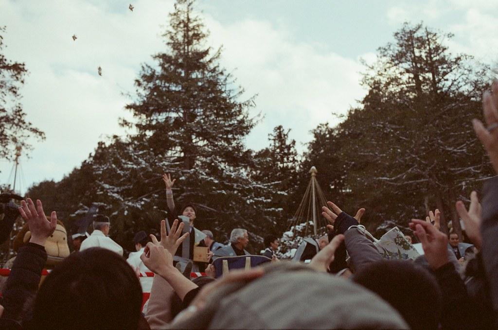 北海道神宮節分祭 Hokkaido, Japan / Fujifilm 500D 8592 / Nikon FM2 2016/02/04 北海道神宮節分祭,有對妖怪丟納豆的儀式,第一次搞懂原來丟納豆的祭典是怎樣的一回事,很新鮮。  那時候天空又飄起雪來,有點冷,站在那裡等很久,附近的居民慢慢聚集在舞台前,等到開始丟祈福的納豆時,大家都往前擠,有點恐怖!  不過真的還滿好玩的,這是這趟旅行第二次來到北海道神宮。  後來回到札幌車站附近的郵便局買明信片,看到電視在轉播各地的節分祭活動,稍微停下來看一下新聞,看看有沒有拍到我!  Nikon FM2 Nikon AI AF Nikkor 35mm F/2D Fujifilm 500D 8592 1114-0022 Photo by Toomore