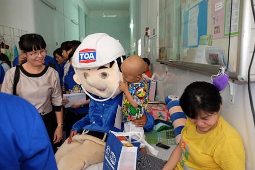 """Niềm vui của một bệnh nhi khi nhận được phần quà từ đại diện Sơn TOA trong chiến dịch """"Xuân Yêu Thương"""" 2016"""