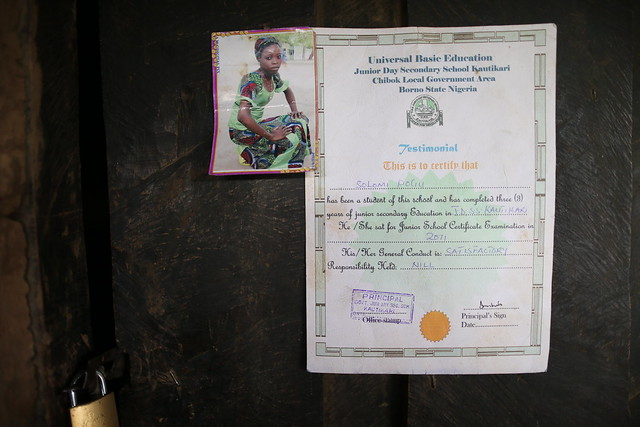 "A portrait photograph and certificate belonging to Solomi Pogu are pasted on the door of her home <br /> <br /> ""Why did the government allow this?""<br /> <br /> Mary Pogu gave birth to 10 children and Solomi was her seventh, but then two died and Boko Haram now have a third. When Solomi, 17 at the time, was abducted, her mother wept, not just for Solomi but also for the other two children she had lost. <br /> <br /> Her daughter had wanted to finish her exams and immediately go for further education to fulfill her ambition of becoming a teacher. Now, Mary regrets ever letting the girl go to school. &quot;My last son said he wanted to go to school but I told him, no way.&quot;<br /> <br /> What she can't understand was how such a thing could be allowed to happen. How could a child be kidnapped from school?<br /> <br /> ""When a child goes to school, is she not the responsibility of the government?"" she asked through tears. ""Why did the government allow this Boko Haram to carry away my child?"""