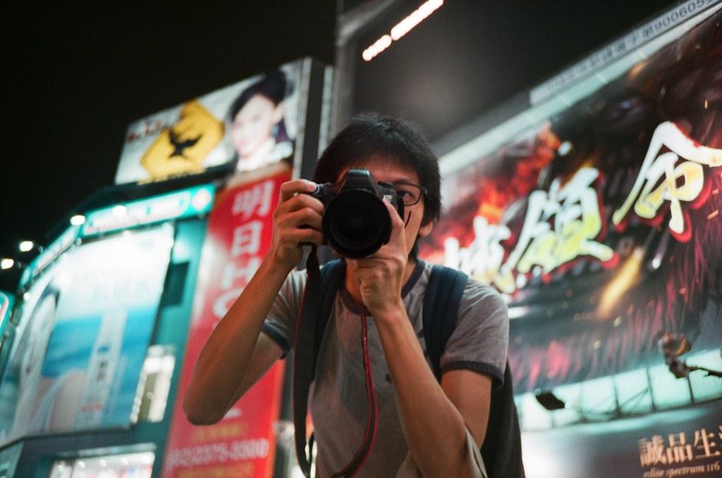 我 西門町 Taipei, Taiwan / FUJICOLOR PRO 400H / Lomo LC-A+ 原來從別人的眼中看到我拍照的樣子是這樣,原來我真的不會閉上眼睛。  其實拍數位的時候因為是自動對焦,所以也就不會太刻意去注意觀景窗內的對焦狀況,我反而是用左眼去看我想要拍的人的瞬間表情與周圍場景的互動。  所以我常常就是這樣拍照,反正現在相機越做越小,也不會擋到左眼,就善加利用吧!  Lomo LC-A+ FUJICOLOR PRO 400H 3186-0034 2015-11-07 ~ 2015-11-14 Photo by Toomore