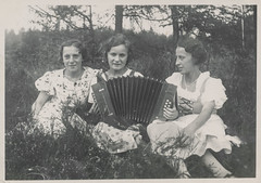 Young girls sitting in the grass playing an accordion