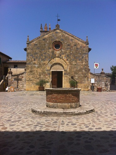 The old well and the Romanic style church of Monteriggioni