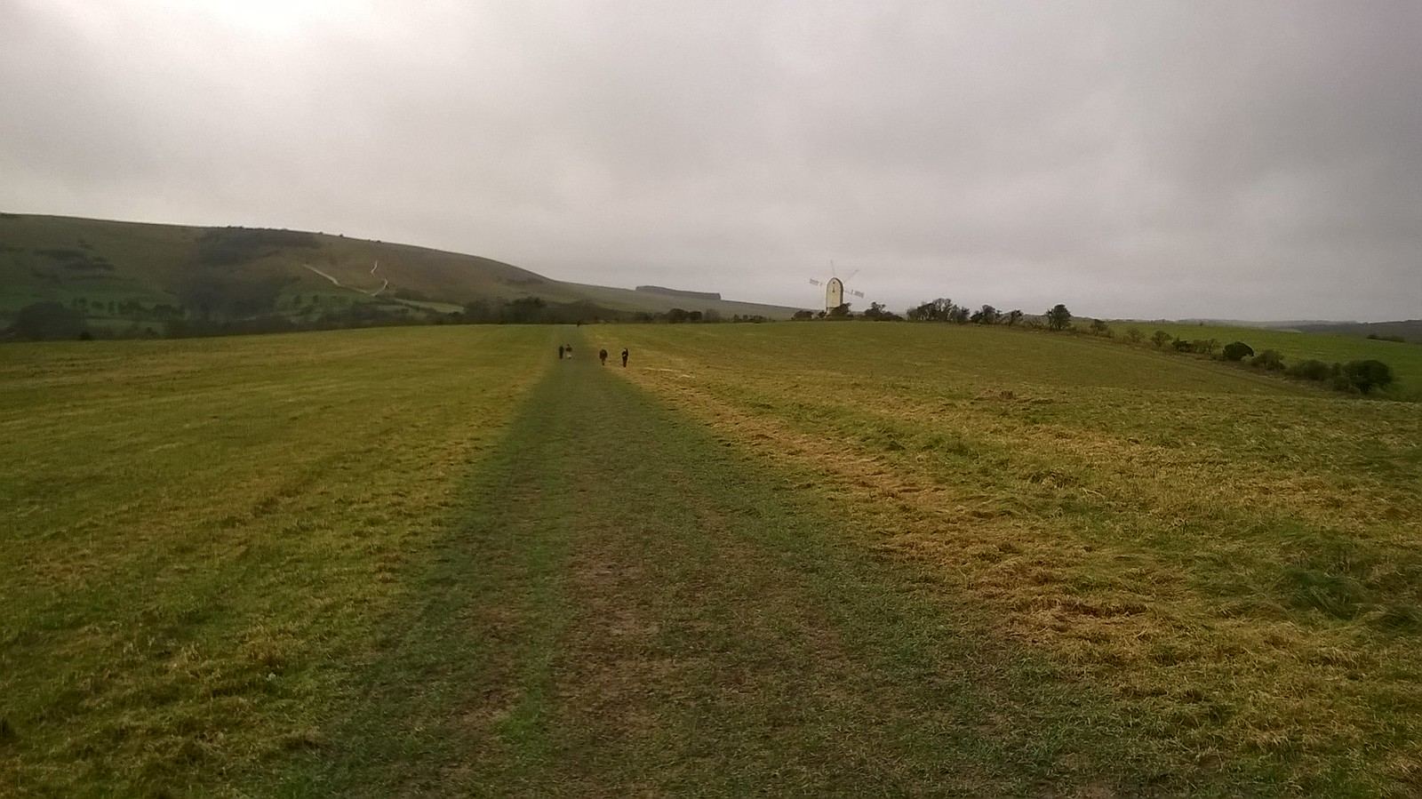 Saturday Walkers approaching renovated windmill near Kingston at the foot of the South Downs.