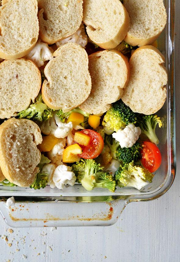 Leg de sneetjes stokbrood dakpansgewijs bovenop de groenten.