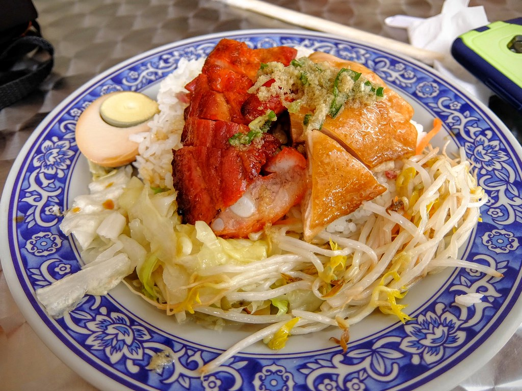 叉燒拼雞飯,有叉燒肉+油雞,底下是滿滿的飯,旁邊則有二樣配菜和半顆滷蛋