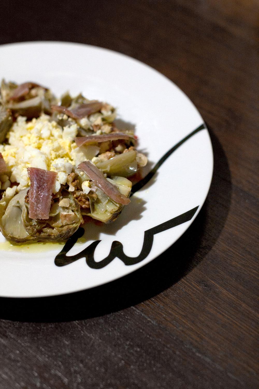 Alcachofas confitadas con huevo duro, anchoas y nueces