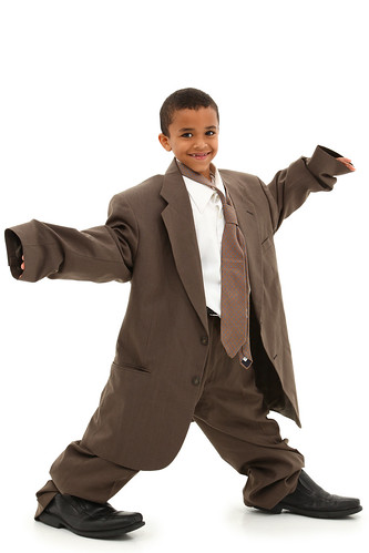 Adorable Handsome Black Boy Child in Baggy Business Suit laughing and walking over white background.