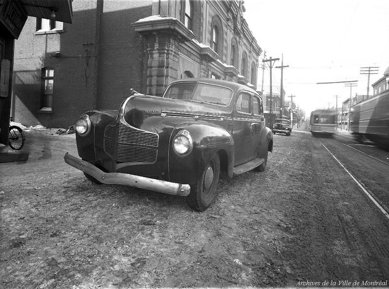 Scène d'un vol à main armée avec une voiture Dodge au premier plan. - 3 février 1945. VM095-Y-1-2-1-D02. Photo par Henri Thibodeau. Archives de la Ville de Montréal.