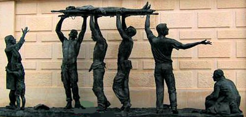 A statue of 4 men holding up a stretcher; located in the National Memorial Arboretum in the UK