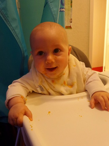baby in a high chair, smiling and covered in sweet potato mush