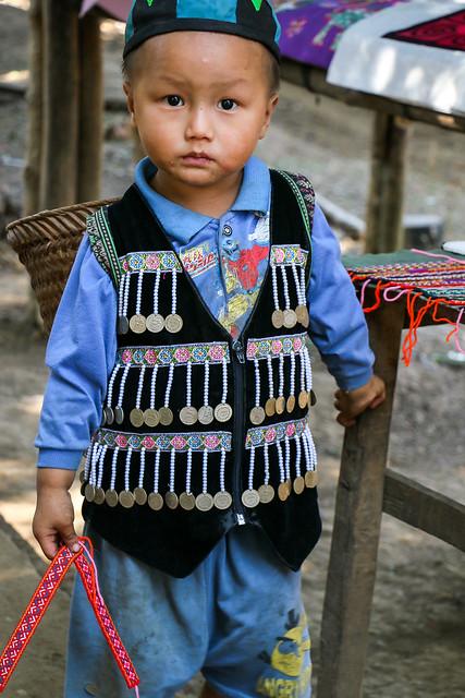 Boy wearing ethnical decorated vest, Hmong village near Luang Prabang, Laos ルアンパバーン郊外のモン族村、民族衣装ベストを着た少年