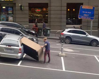 Imagen graciosa de hombre metiendo sofá en coche