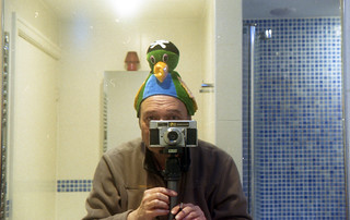 reflected self-portrait with Durst Automatica camera and parate hat