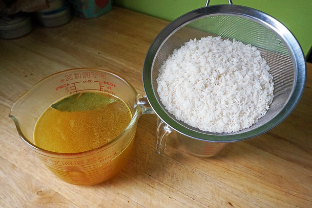 A large measuring cup full of golden stock, a bay leaf floating in it, sits next to a wire strainer filled with just-washed rice. (Which is really just about all that goes into this dish!)