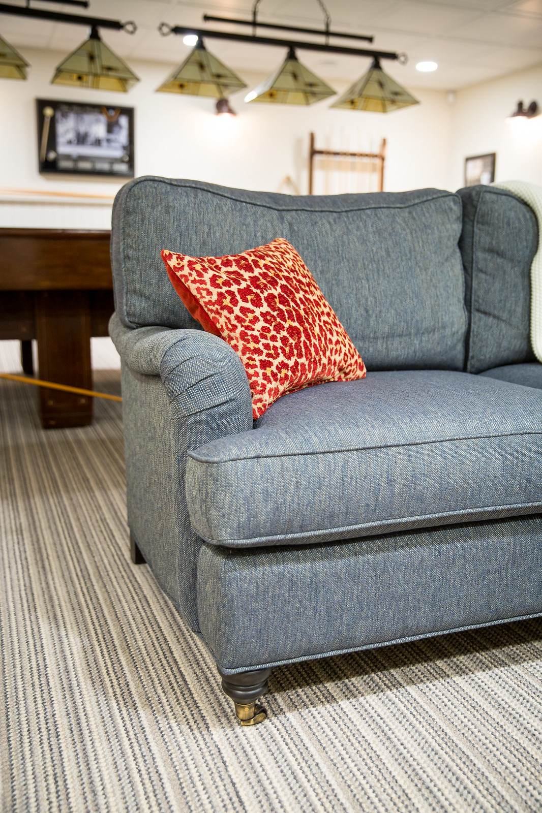 William Birch sofa from Gresham House upholstered in a denim blue tweed fabric with red animal print toss cushion
