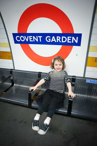 Little girl sitting on a bench with a Covent Garden sign in the background