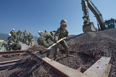 U.S. Navy Builder Constructionman Apprentice Brooklyn Allen, assigned to Naval Mobile Construction Battalion (NMCB) 4, shovels aggregate with Republic of Korea Seabees during pier repair training for Foal Eagle. (U.S. Navy/MCC Lowell Whitman)