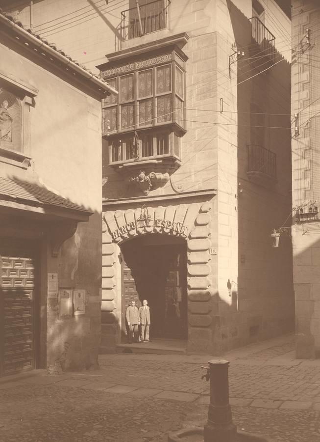 Banco de España en la Calle Cadenas, junto a la Iglesia de San Nicolás, en su emplazamiento primitivo. (La portada está hoy en la Iglesia de Santa Bárbara). Archivo Municipal de Toledo