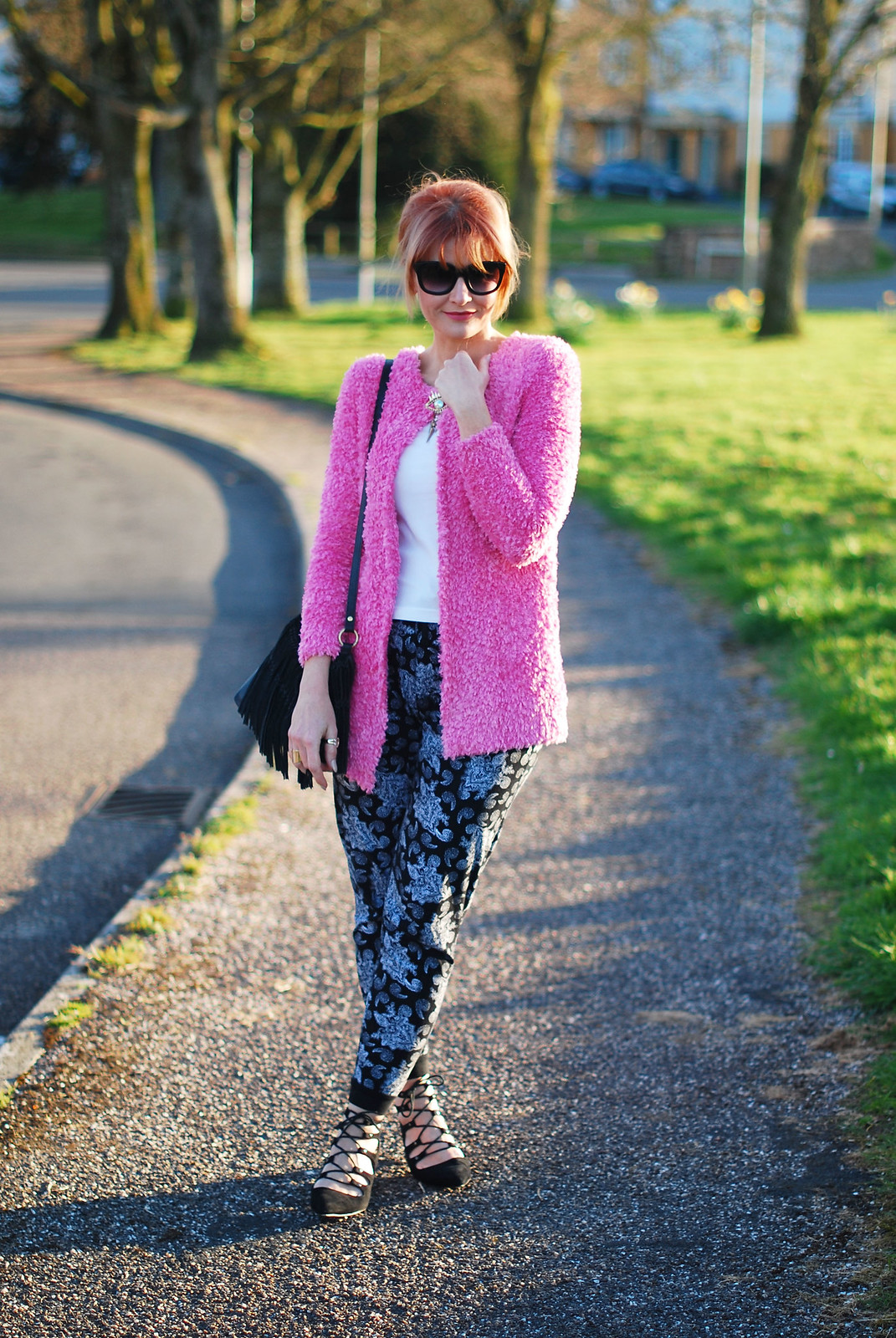 Spring style: Fluffy pink cardigan, paisley joggers, black lace up pointed flats, up do, cat eye sunglasses, evil eye brooch