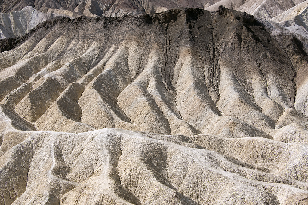 Deeply eroded lake beds capped by dark basalt, Zabriskie Point, Death Valley, Inyo County, California